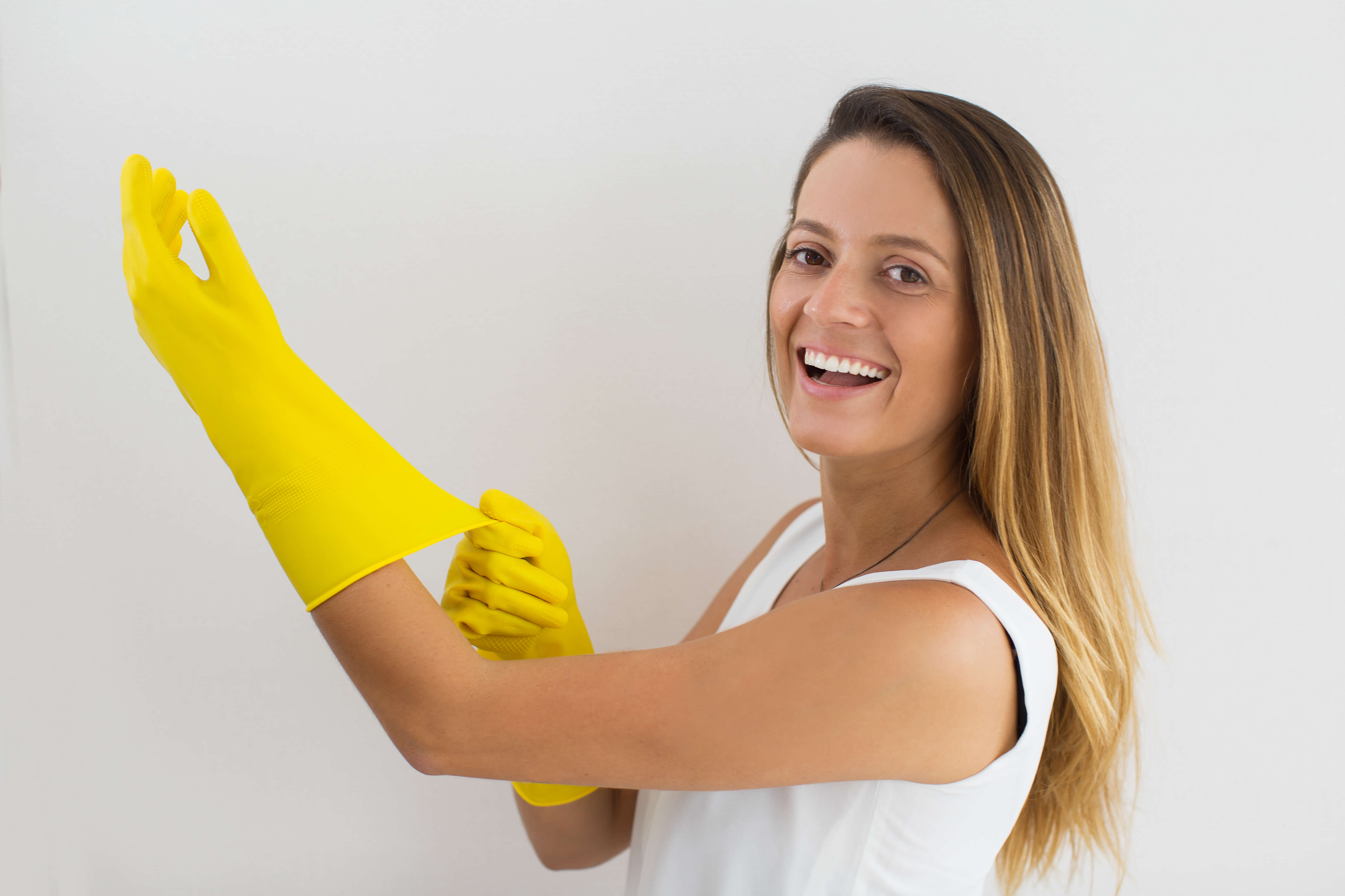 Excited young housewife putting rubber glove on hand and looking at camera. Happy woman loving cleaning. Cleaning at home concept