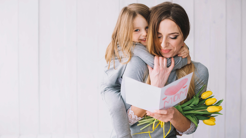cadeau original pour fête des mères petite fille accrochée au cou de sa mère qui lui offre des fleurs et une carte pour sa fête