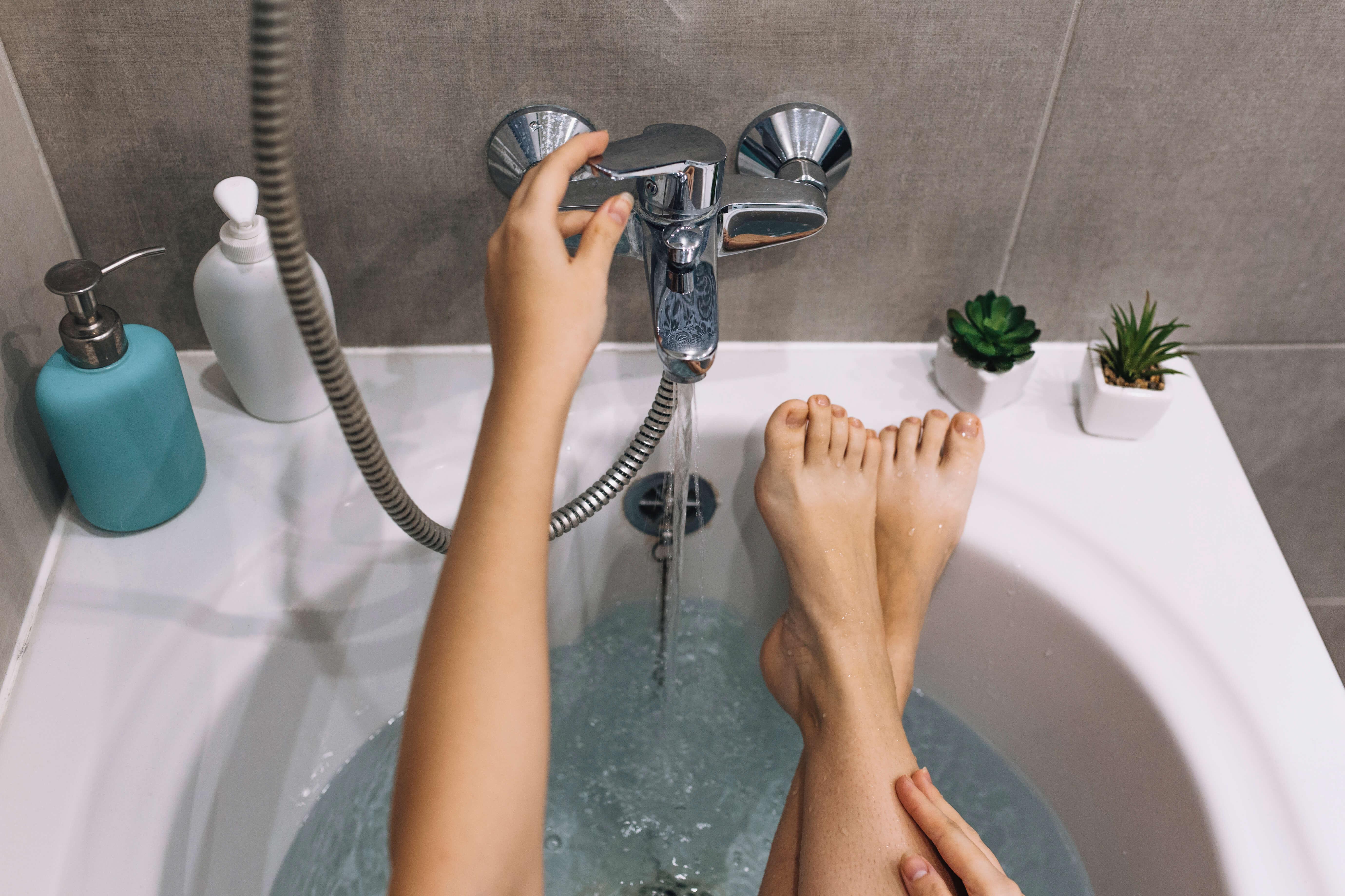 la détox par les pieds dans un bain avec un robinet ouvert