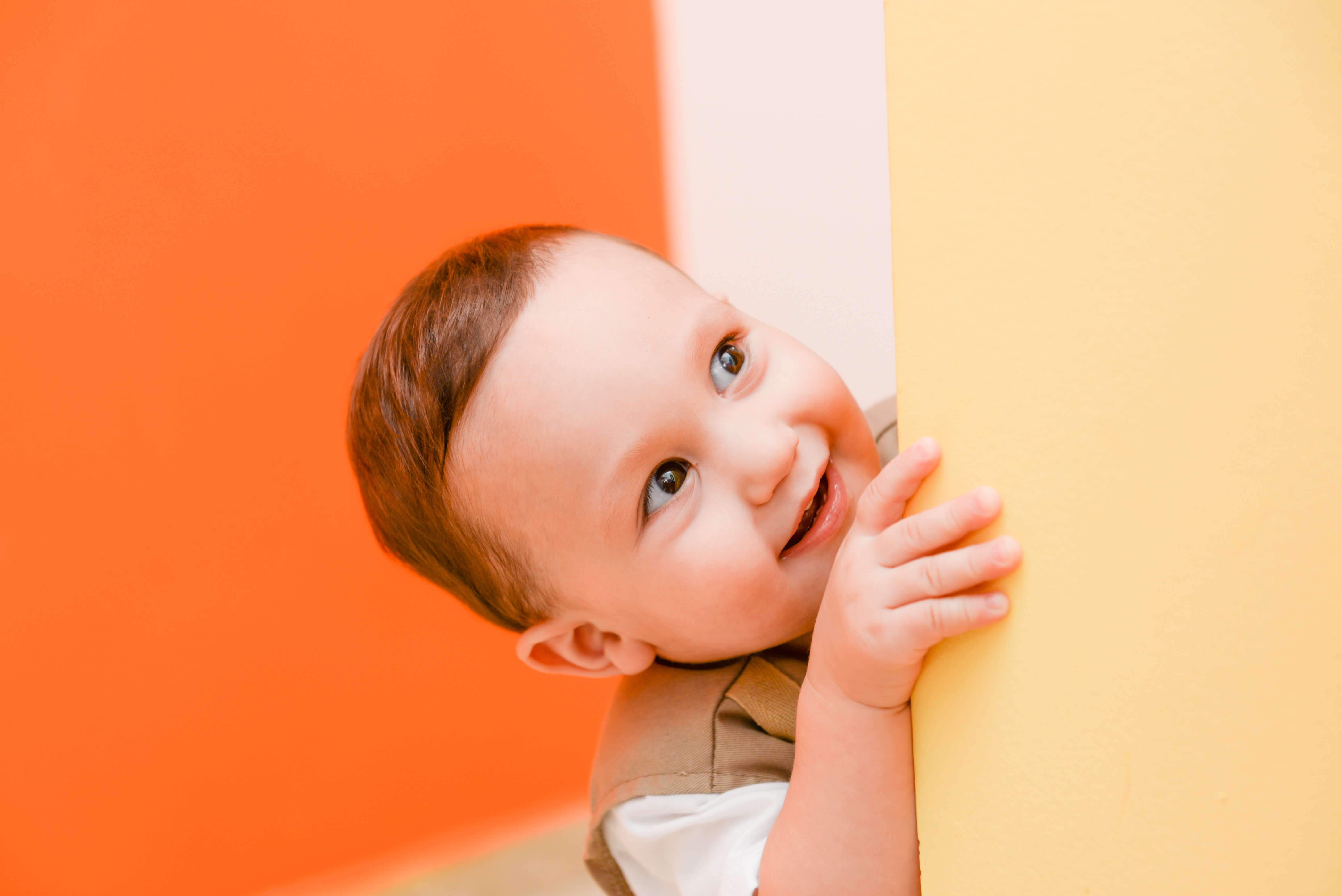 comment enseigner le ménage à ses enfants ? enfant qui se cache derrière un mur beige