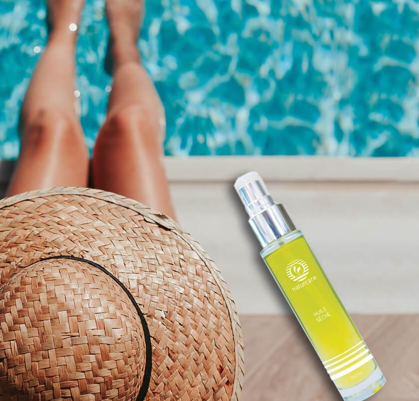 huile sèche au bord d'une piscine avec une femme