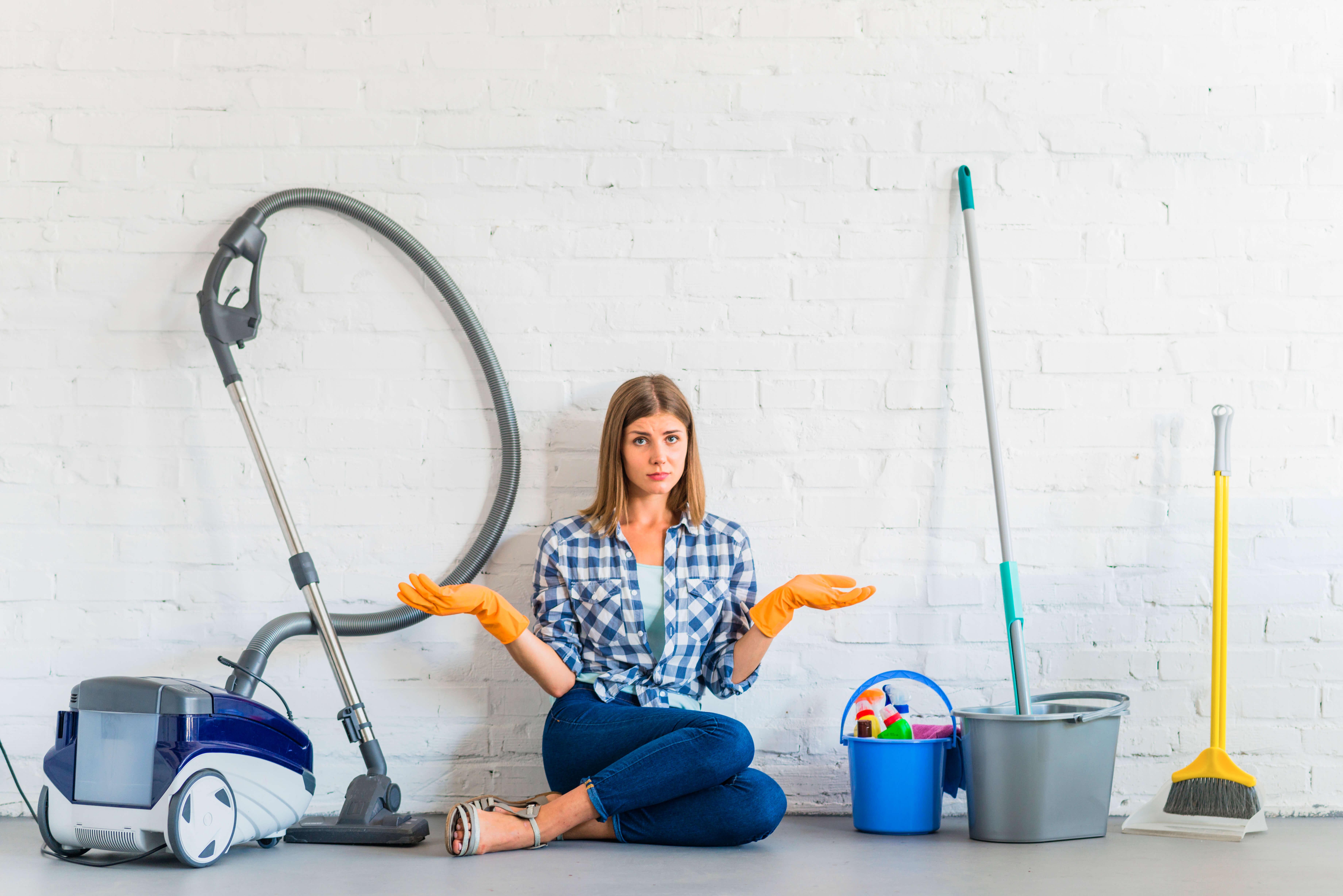 jeune femme qui est entourée de produits et matériel pour faire le ménage
