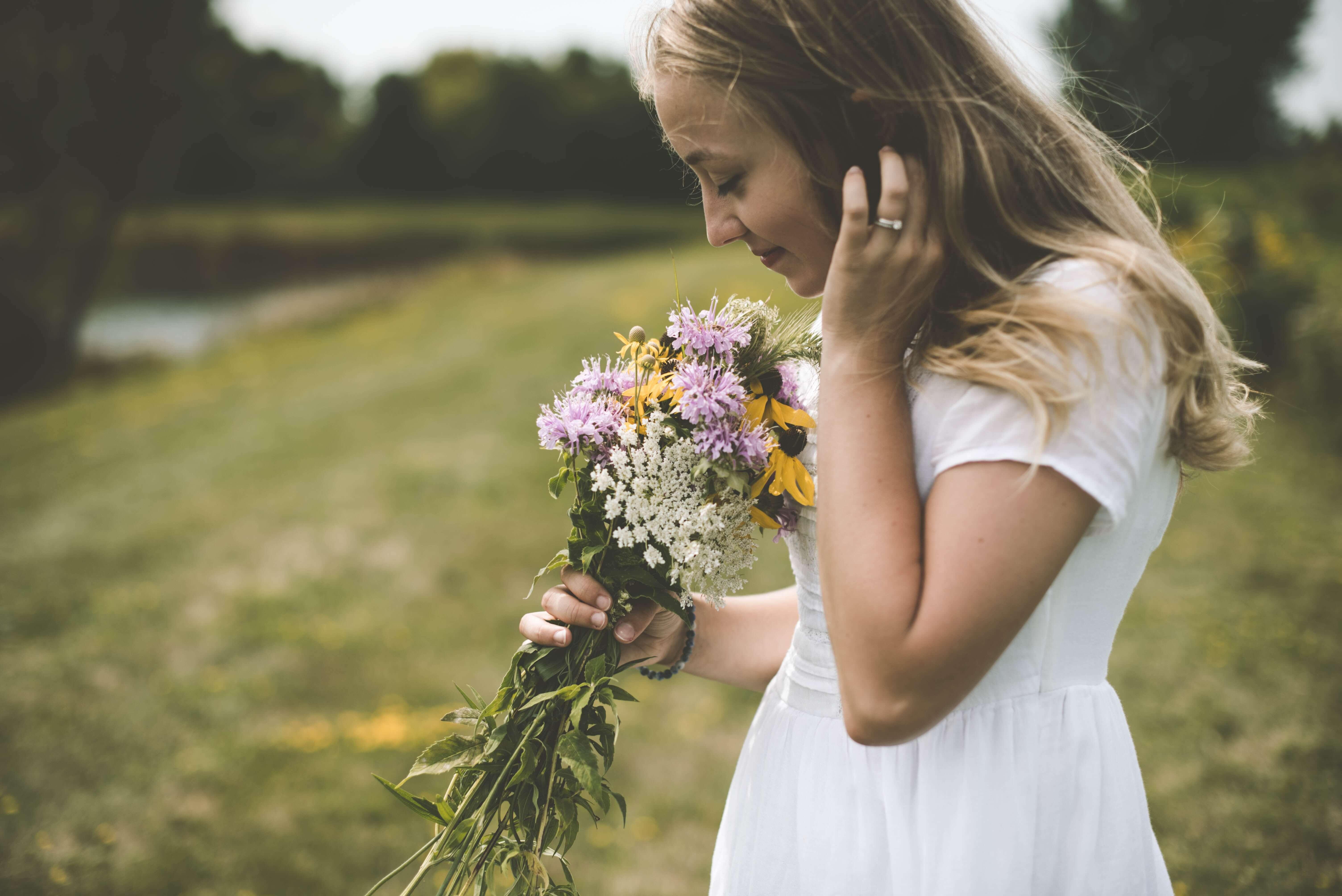 Le pouvoir des odeurs pour contribuer au bien-être, jeune femme qui sent un bouquet de fleurs dans les champs elle porte une robe blanche et est blonde
