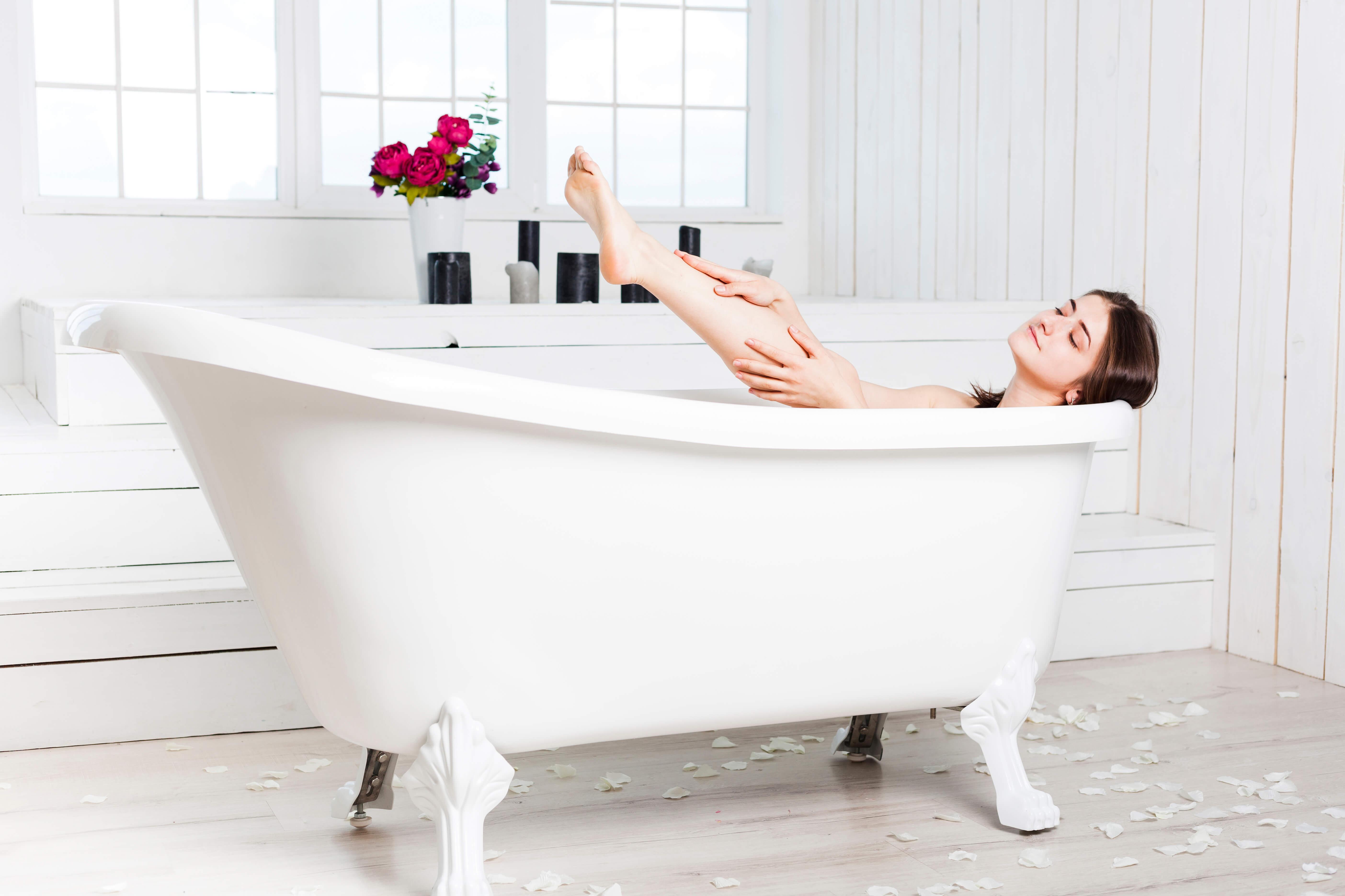 femme qui prend un bain dans une baignoire blanche salle de bain de luxe