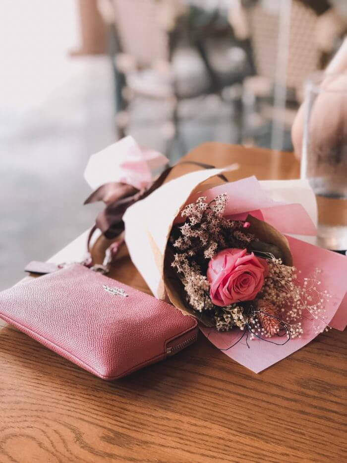 quel cadeau offrir à une femme pour la saint valentin bouquet de rose et porte feuille rose posés sur une table